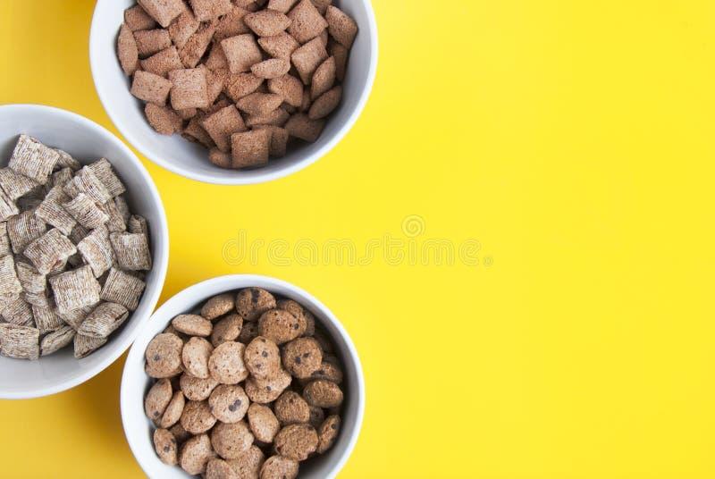 Шары всех muesli, granola и oatmeals зерна с космосом экземпляра Изолировано на желтой предпосылке Взгляд сверху Ежедневная еда з стоковые фотографии rf