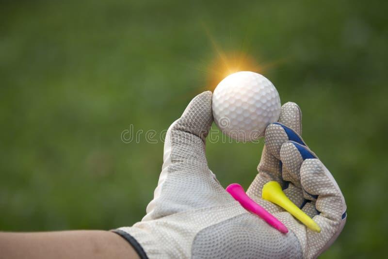 Шары для игры в гольф и тройник в руках которые несены с белыми перчатк стоковые фотографии rf
