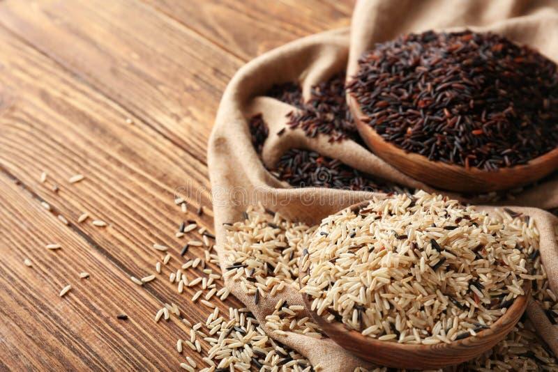 Шары с различными видами риса на деревянном столе стоковые фотографии rf