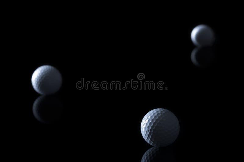 Шары для игры в гольф изолированные на черной предпосылке стоковое изображение rf