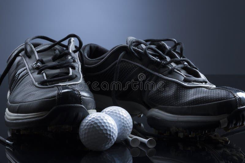 Шары для игры в гольф, тройники и ботинки на синей предпосылке стоковое фото