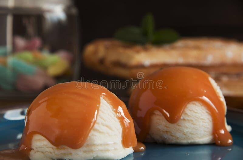 Шар белого ванильного мороженого с соусом карамельки стоковые изображения