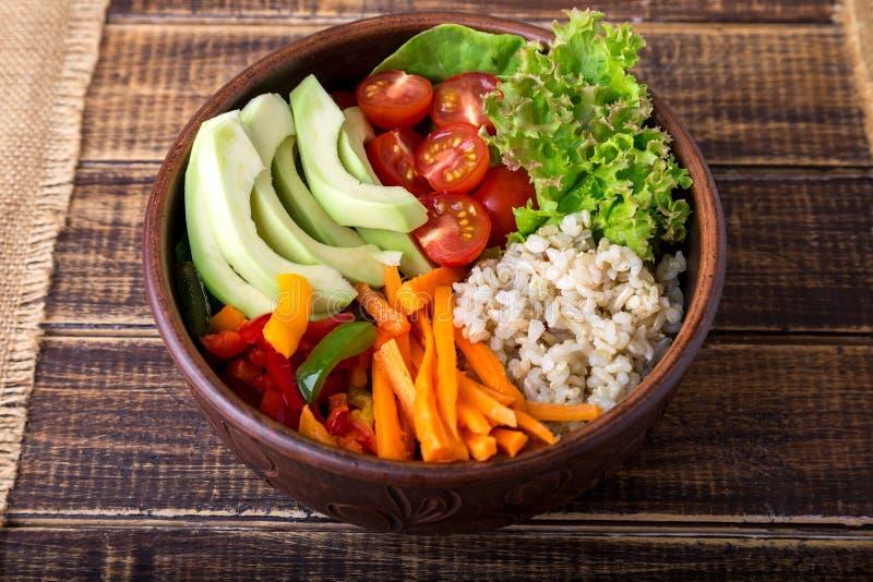 Шар Будды Vegan на деревянной предпосылке Взгляд сверху Шар с морковью, салатом, томатами вишней, перцем, авокадоом и кашой Veget стоковые фото