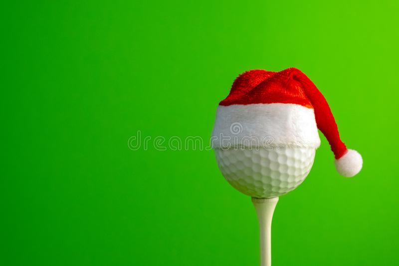 Шар для игры в гольф в красной шляпе Санта Клауса установил на тройнике Концепция спорт на теме рождества и Нового Года Зеленая п стоковые фото
