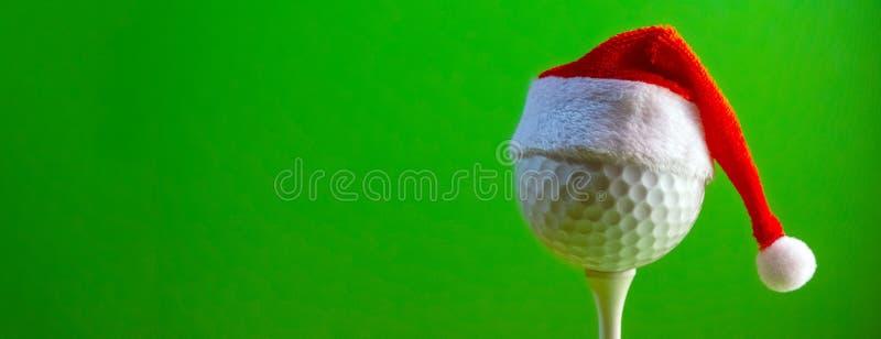Шар для игры в гольф установил на тройнике носит шляпу сувенира Санта Клауса Пробел для открытки для игрока в гольф для того чтоб стоковая фотография