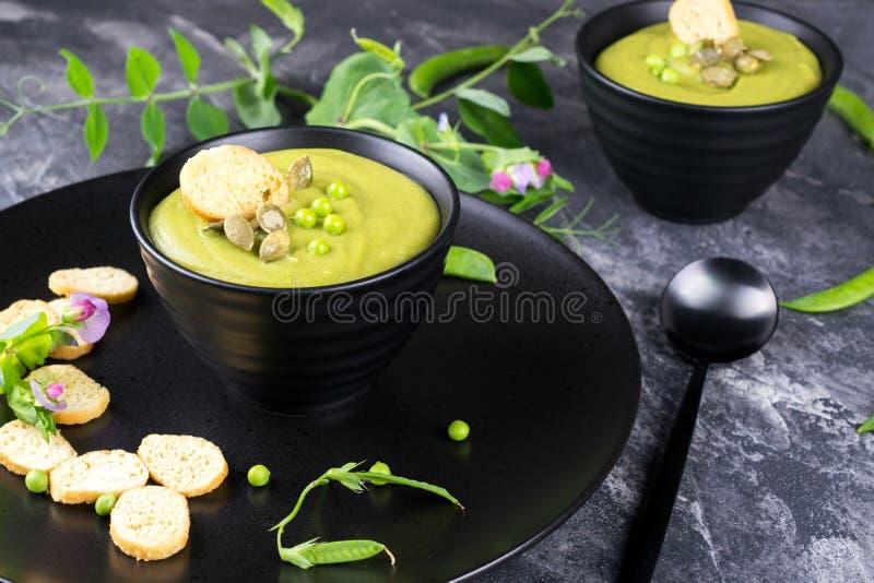Шар домодельного зеленого супа гороха весны покрыл с семенами тыквы, гренками На темном камне стоковые изображения rf