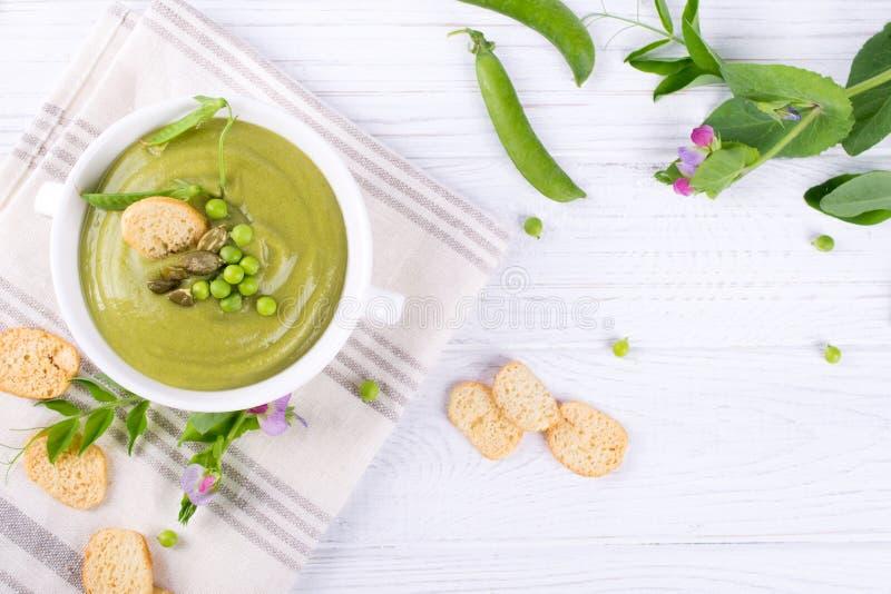 Шар домодельного зеленого супа гороха весны покрыл с семенами тыквы, гренками На белой предпосылке Плоское положение стоковая фотография