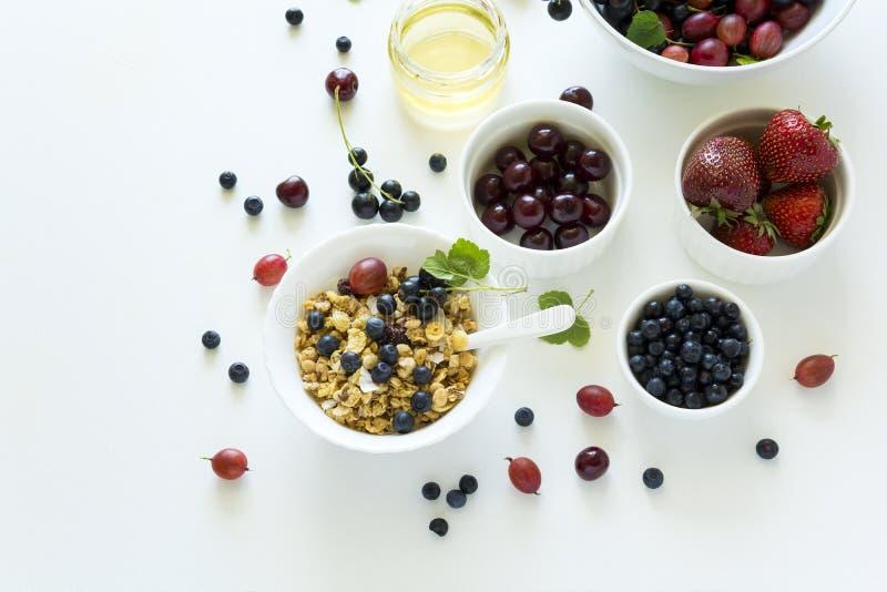 Шар домодельного granola с клубникой, голубикой, вишней, крыжовником, черной смородиной и медом на белой деревянной предпосылке стоковое фото