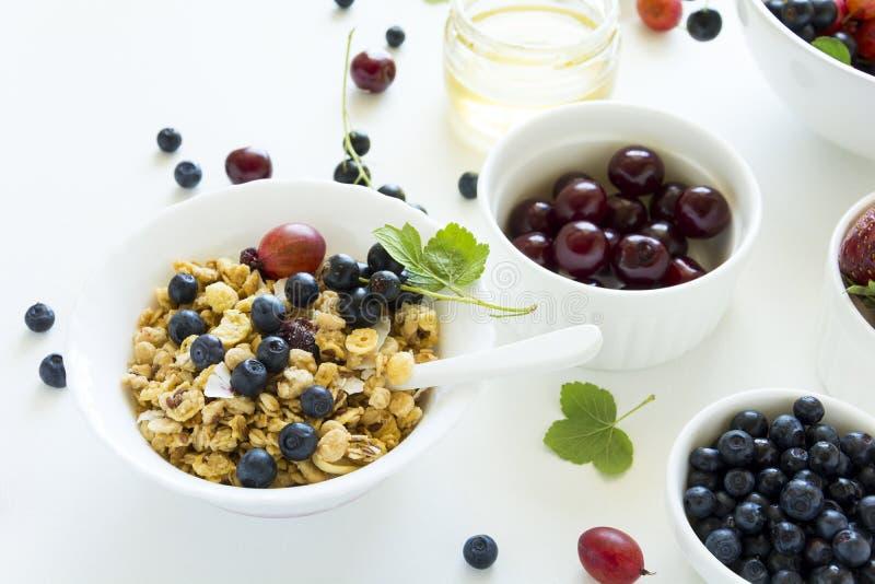 Шар домодельного granola с клубникой, голубикой, вишней, крыжовником, черной смородиной и медом на белой деревянной предпосылке стоковая фотография rf