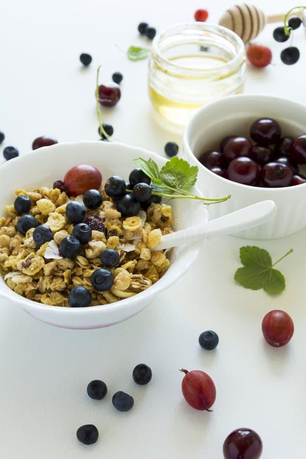 Шар домодельного granola с клубникой, голубикой, вишней, крыжовником, черной смородиной и медом на белой деревянной предпосылке стоковые изображения