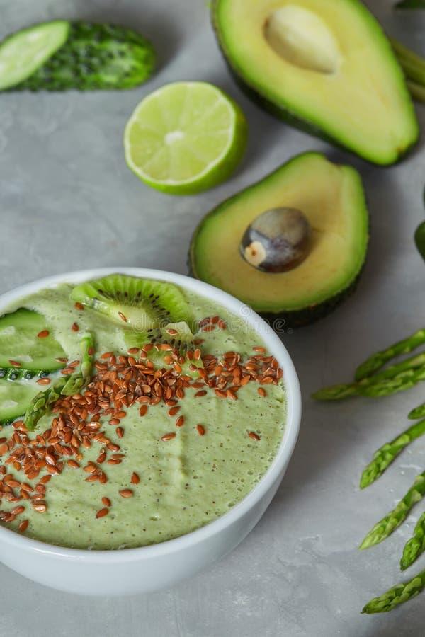 Шар зеленого шпината smoothy покрыл с семенами огурца, авокадоа и льна на каменной предпосылке стоковые изображения