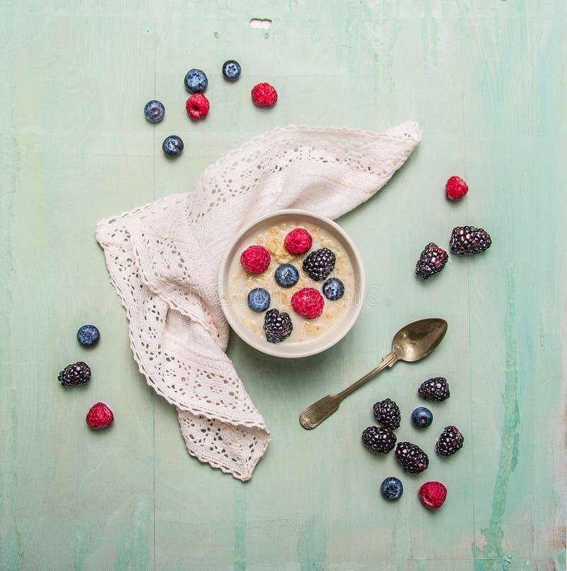Шар каши овсяной каши с ягодами на голубой деревенской деревянной предпосылке стоковые фотографии rf