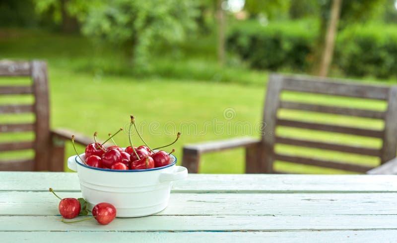 Шар свежих сочных вишен на таблице в саде стоковое фото rf