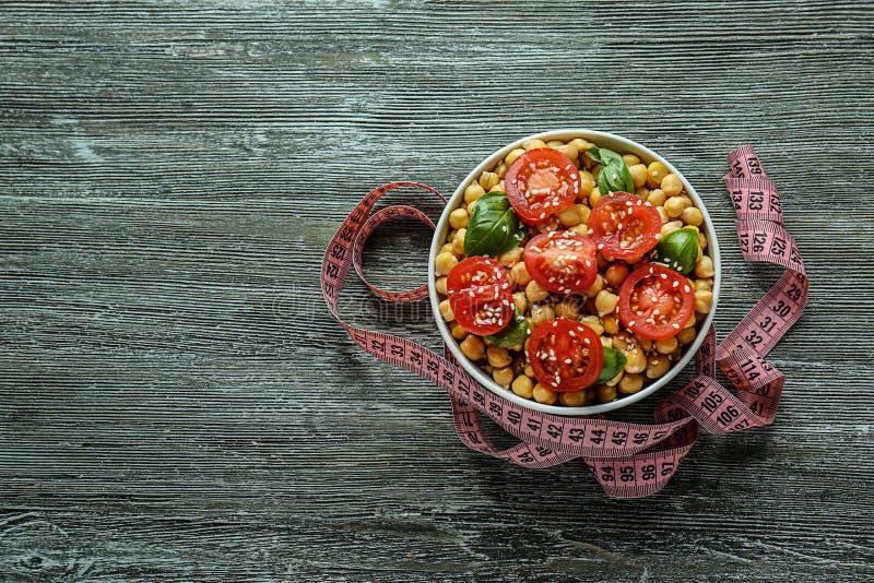Шар с нутом, томатами и измеряя лентой на деревянном столе E стоковые фото