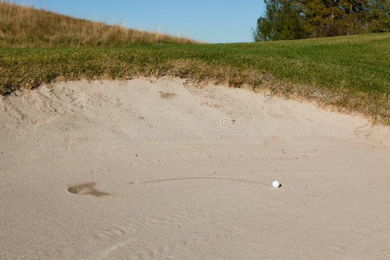 Шар для игры в гольф в песколовке стоковое фото rf