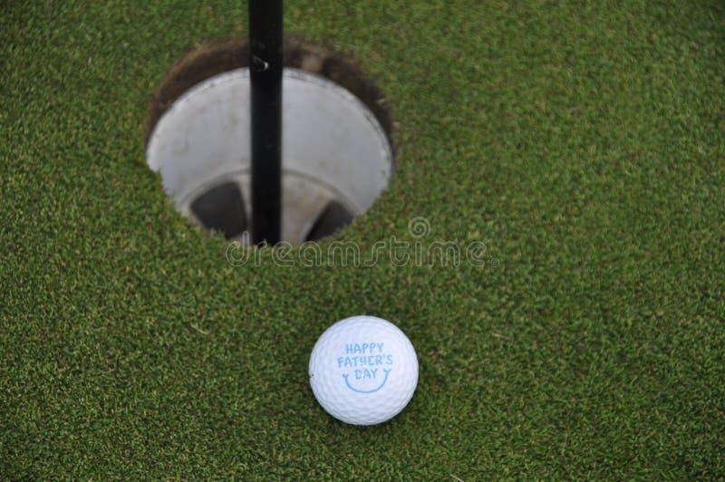 Шар для игры в гольф на зеленом цвете гольфа стоковое изображение