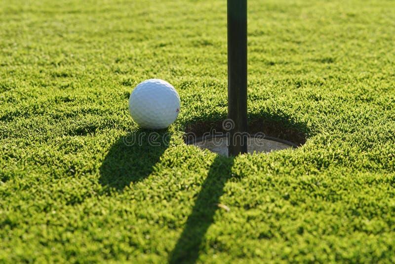 Шар для игры в гольф на зеленом цвете стоковое изображение