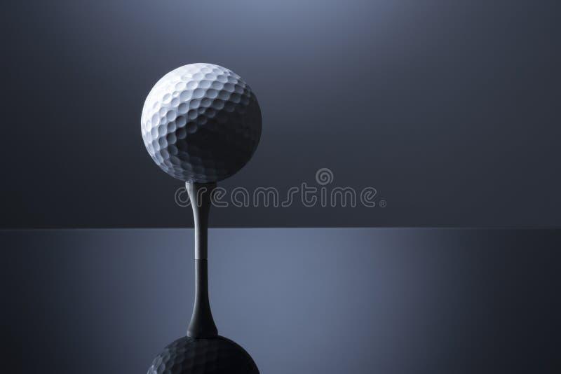 Шар для игры в гольф на тройнике изолированном на синей отражательной предпосылке стоковое фото