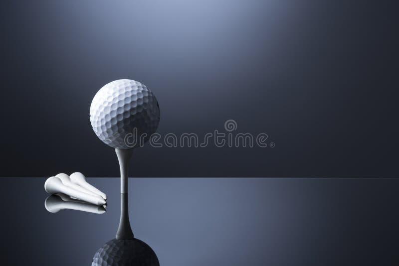 Шар для игры в гольф на тройнике изолированном на синей отражательной предпосылке стоковые фотографии rf