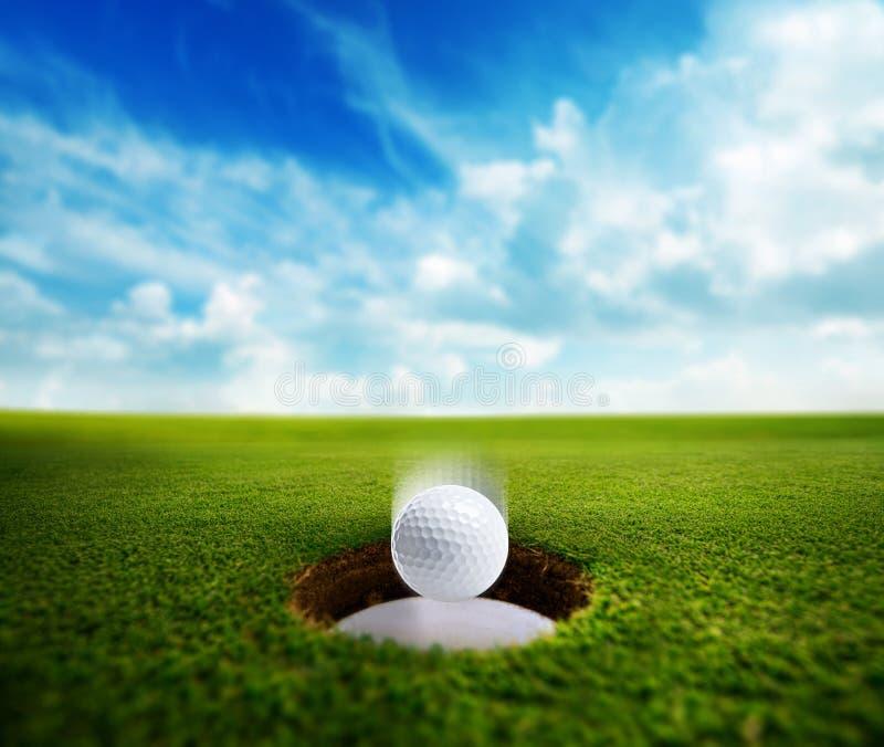 Шар для игры в гольф падая в отверстие стоковые фотографии rf