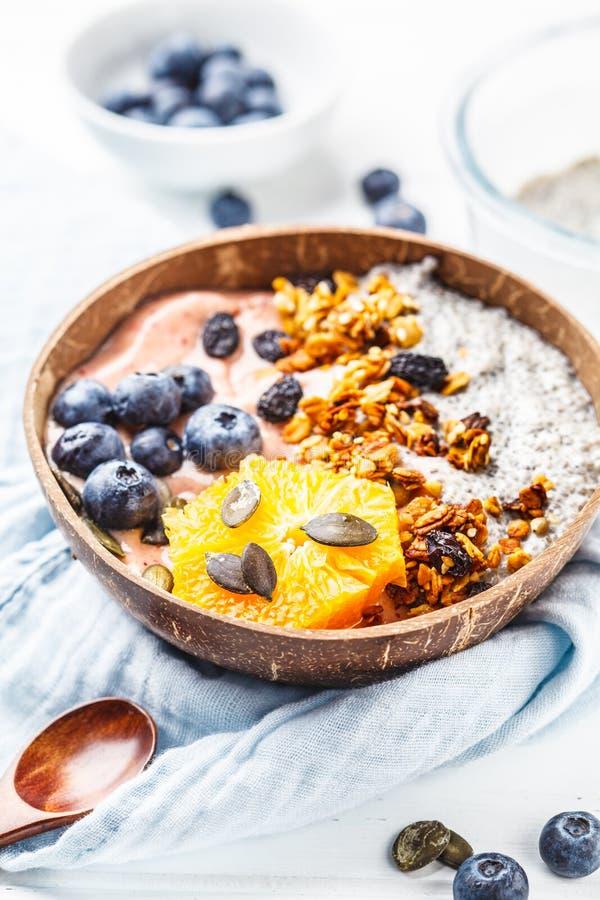 Шар smoothie завтрака с пудингом, ягодами и granola chia в раковине кокоса на белой деревянной предпосылке стоковое фото