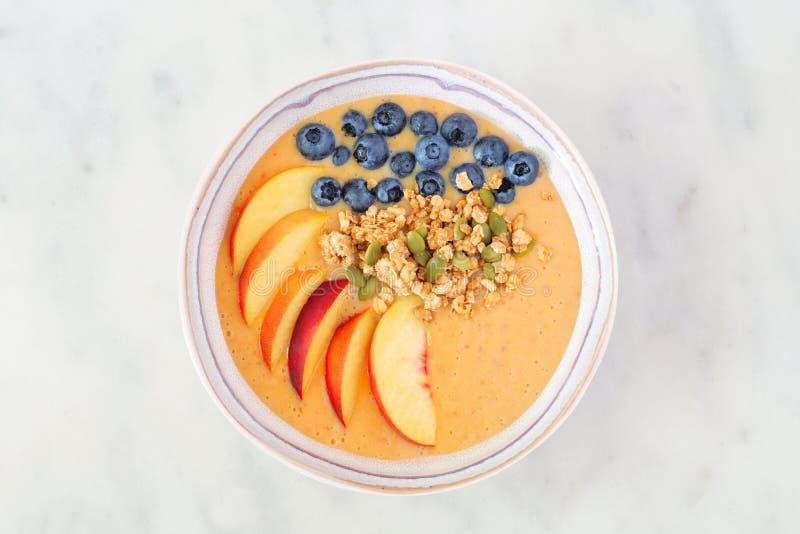 Шар smoothie персика с голубиками и granola, взглядом сверху на мраморной предпосылке стоковое изображение rf