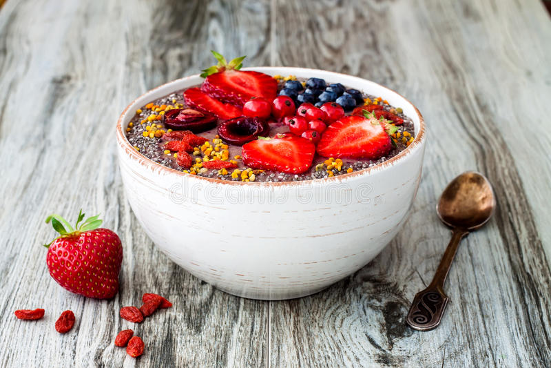 Шар smoothies superfoods завтрака Acai с семенами chia, цветнем пчелы, отбензиниваниями ягоды goji и арахисовым маслом надземно стоковое фото rf