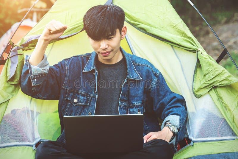 Шатер кофе ноутбука молодого человека располагаясь лагерем стоковое фото