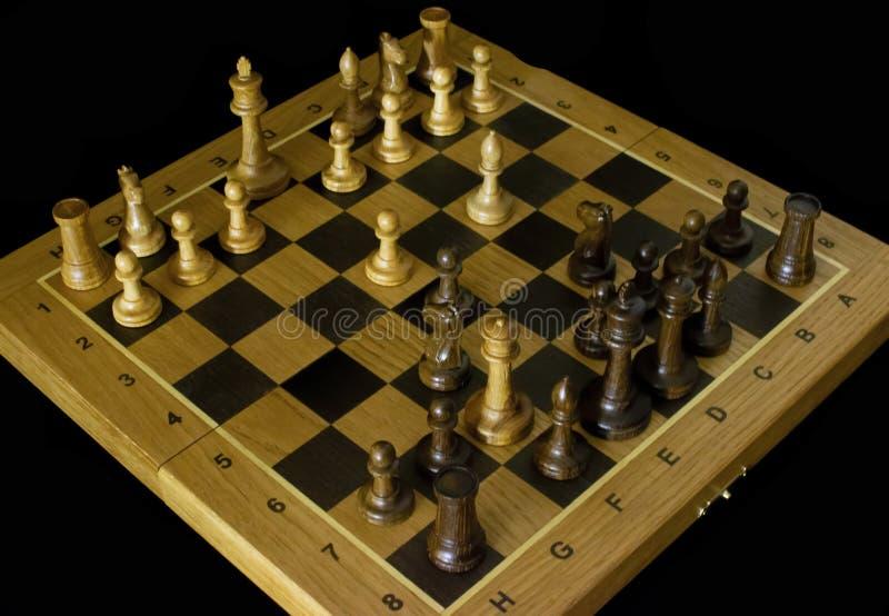Шахматы Шахматная доска на черной предпосылке стоковое изображение