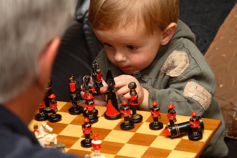 шахмат мальчика играя детенышей стоковые фотографии rf