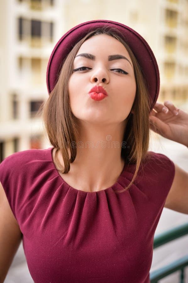 Шаловливая дама в темноте - красная посылка шляпы и платья стоковое изображение rf