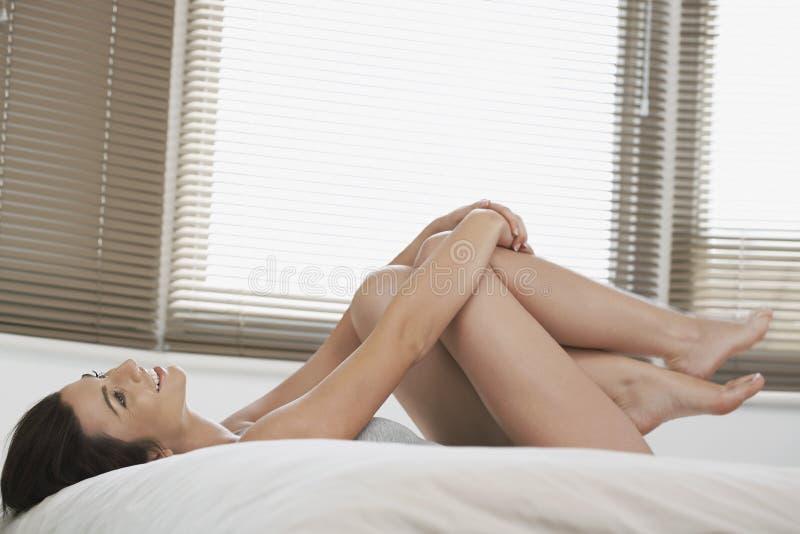 Шаловливая женщина обнимая колени пока лежащ в кровати стоковая фотография rf
