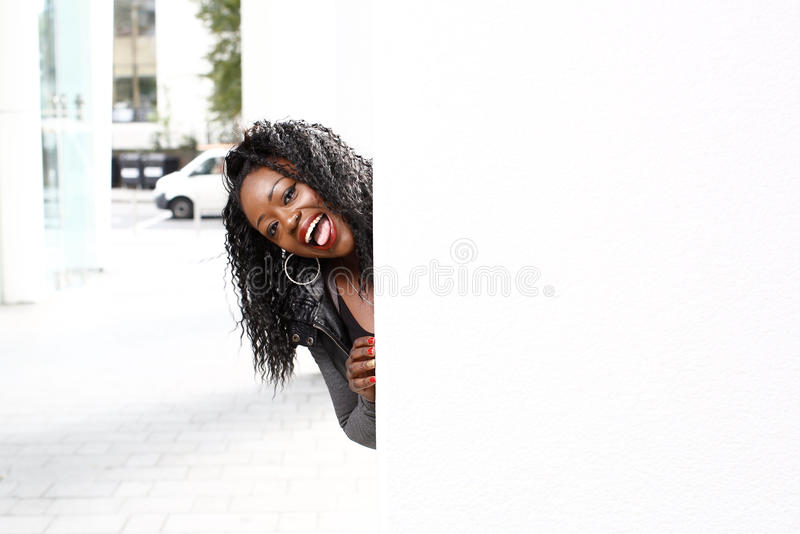 Шаловливая молодая женщина peeking вокруг штендера стоковое фото rf