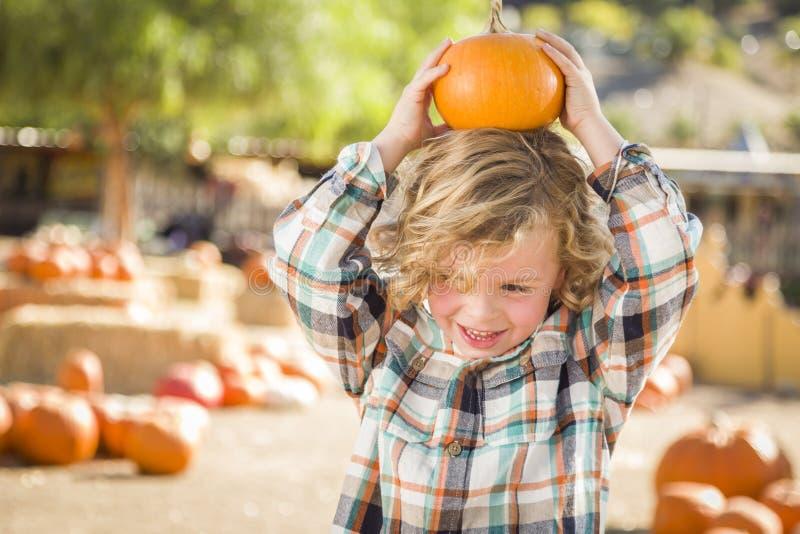 Шаловливый мальчик держа его тыкву на заплате тыквы стоковая фотография