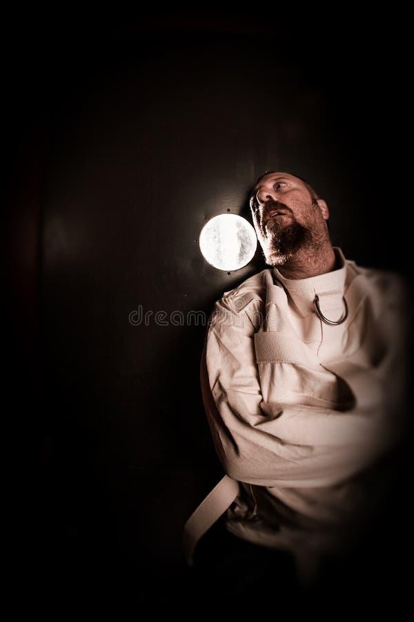 Шальная персона в клетке нося смирительную рубашку стоковые фотографии rf