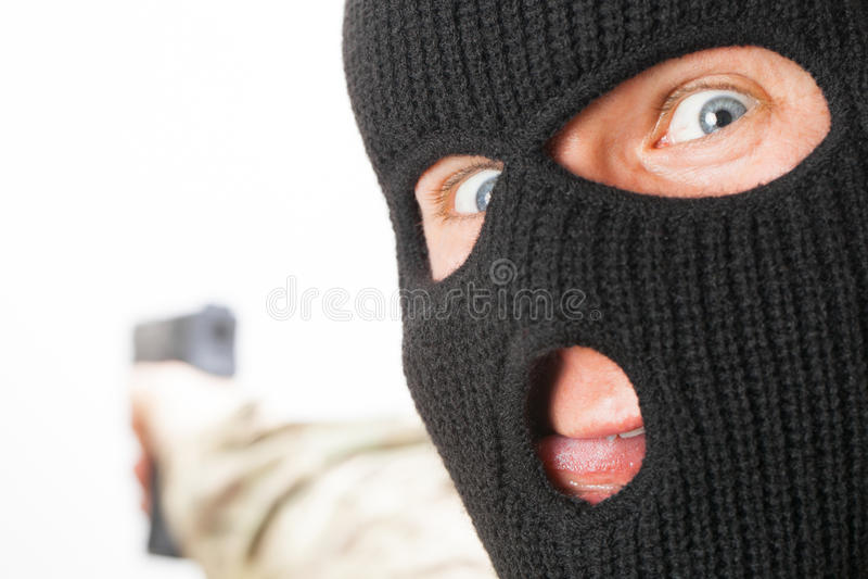 Шальной человек в черной маске держа оружие стоковое фото