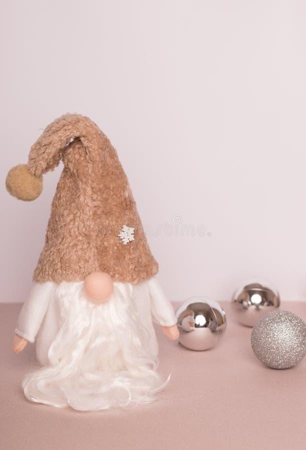 Шведский гном в белых одеждах и бежевой шляпе с 3 серебряными шариками рождества на бежевой предпосылке стоковые изображения