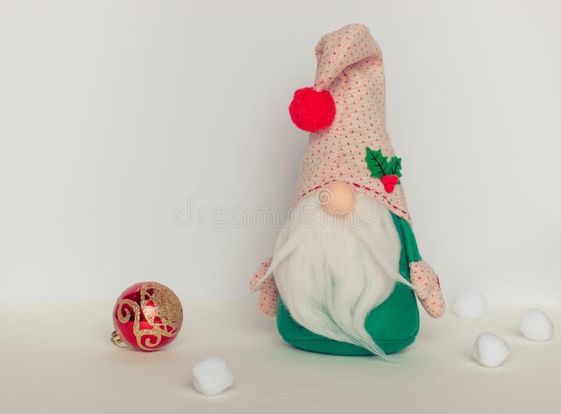 Шведский гном в зеленых одеждах с шариком рождества на белой предпосылке стоковое изображение
