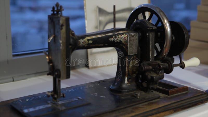 Швейная машина, белошвейка шить на машине и руки ` s женщин Античная швейная машина Франклин Молодая женщина носит стоковые фото