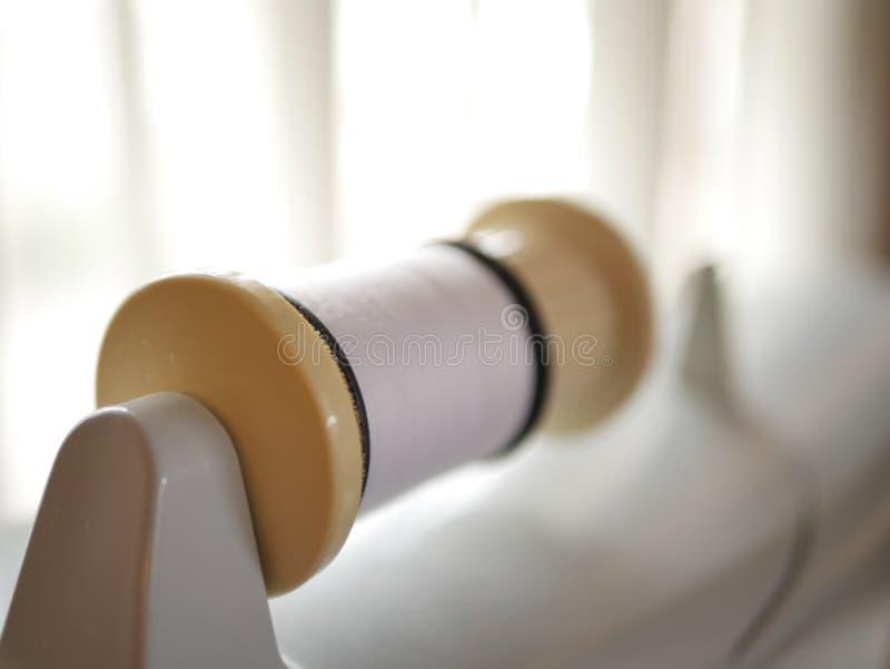 Швейная машина с белой катышкой потока в солнечном свете стоковая фотография