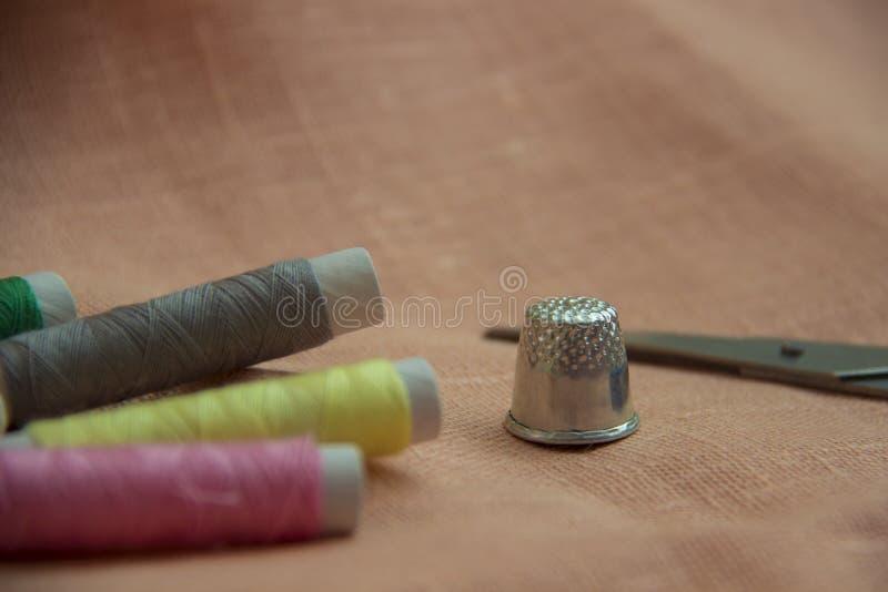 Швейный набор: пестротканый поток, кольцо, ножницы на linen ткани стоковое изображение