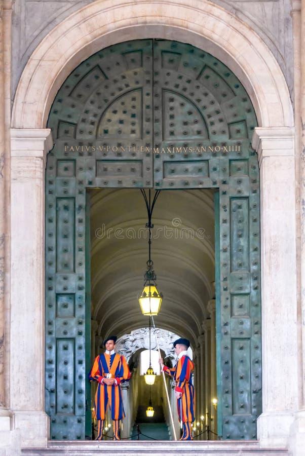 Швейцарские предохранители стоят на бронзовой двери апостольского дворца i стоковые изображения