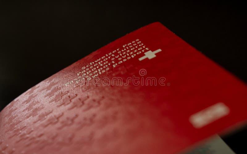 Швейцарский конец пасспорта вверх на черном подданстве Швейцарии предпосылки стоковое изображение