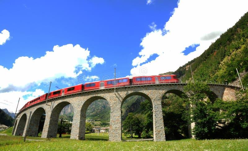 Швейцарский красный поезд Bernina срочное на виадуке Brusio стоковые фотографии rf