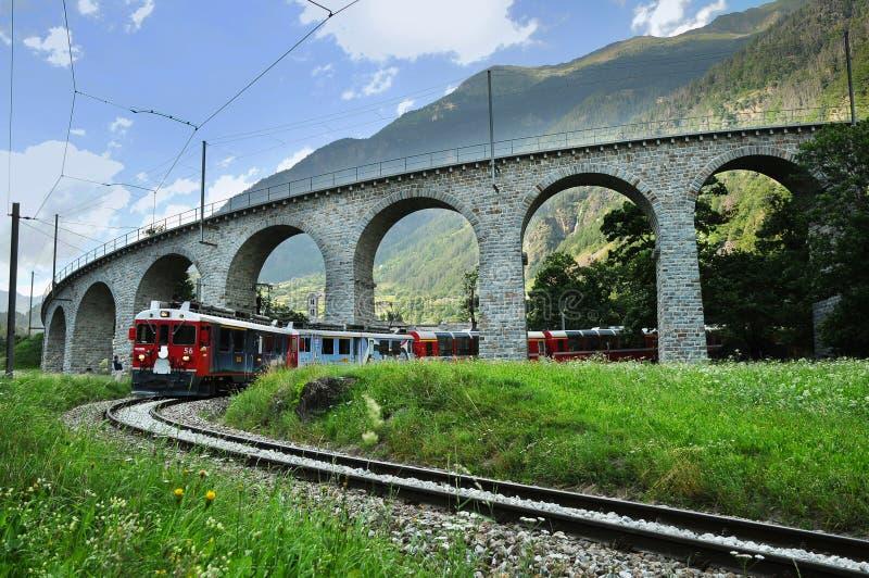 Швейцарский красный поезд Bernina срочное на виадуке Brusio стоковое изображение rf
