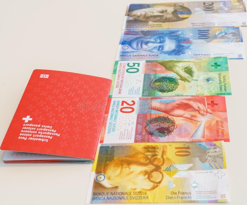 Швейцарский пасспорт и швейцарские франки с новыми 20 и 50 счетами швейцарского франка стоковое фото rf