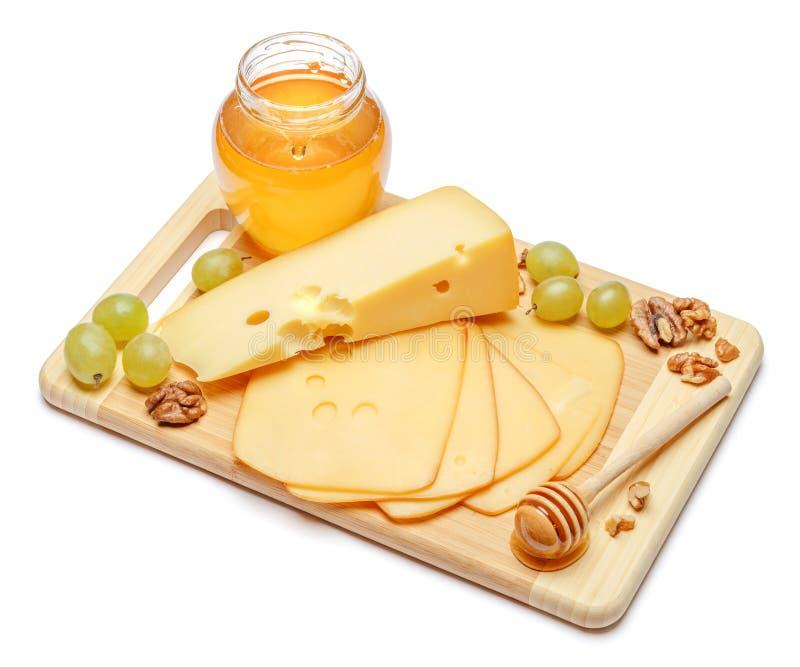 Швейцарский сыр или чеддер и мед на белой предпосылке стоковое фото
