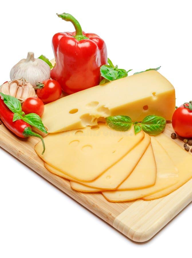Швейцарский сыр или чеддер и овощи на белой предпосылке стоковые изображения