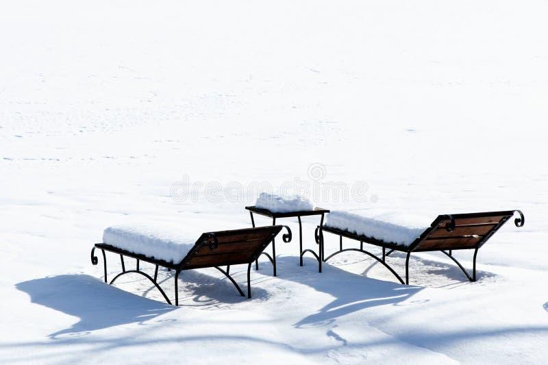 Шезлонги в снеге, загорая в зиме, пустое deckchair на стороне горнолыжного склона, стоковая фотография