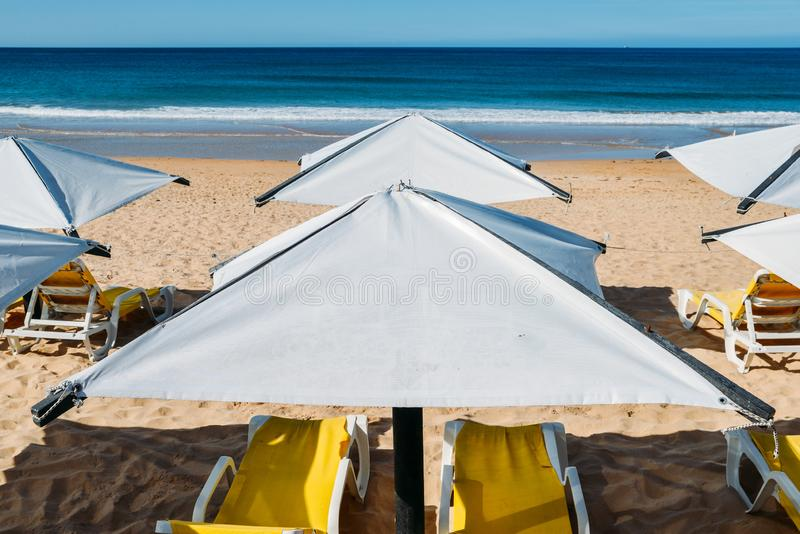 Шезлонги и зонтик пляжа на дезертированной концепции каникул пляжа идеальной стоковые изображения